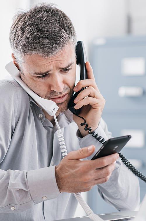 Homme pris entre deux coups de fil et un message sur son smartphone